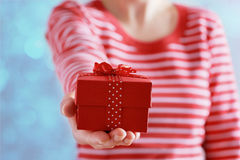 Vrouwenhanden die een gift of een huidige doos met boog van rood lint houden voor Valentijnskaartendag Stock Fotografie