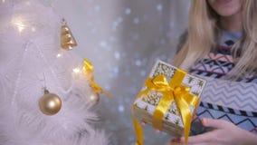 Vrouwenhanden die een gift houden dichtbij Kerstmisboom De Decoratie van het nieuwjaar Sluit omhoog stock footage