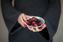 Vrouwenhanden die een kom van frambozen en braambessen, sensueel studioschot houden Stock Fotografie