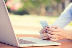 Vrouwenhanden die, gebruikend slimme, mobiele telefoon en computer houden Royalty-vrije Stock Foto