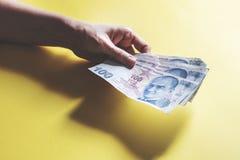 Vrouwenhanden die geld op gele achtergrond houden royalty-vrije stock fotografie