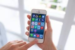 Vrouwenhanden die iPhone met sociaal programma over het scherm houden Stock Afbeeldingen