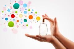 vrouwenhanden die kleurrijke bellen van mooie parfumfles bespuiten Stock Afbeeldingen
