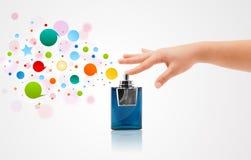 vrouwenhanden die kleurrijke bellen van mooie parfumfles bespuiten Stock Foto