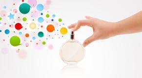 vrouwenhanden die kleurrijke bellen van mooie parfumfles bespuiten Royalty-vrije Stock Afbeelding