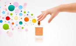 vrouwenhanden die kleurrijke bellen van mooie parfumfles bespuiten Royalty-vrije Stock Foto's
