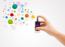 vrouwenhanden die kleurrijke bellen van mooie parfumfles bespuiten Royalty-vrije Stock Fotografie