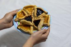 Vrouwenhanden die kleurrijke plaat met abrikoos en bosbessen hamantash de koekjes van Purim houden stock afbeelding