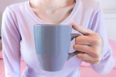 Vrouwenhanden die koffiekop houden Meisje in de mok van de sweaterholding De levensstijl van de ochtenddrank royalty-vrije stock foto's