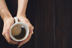 Vrouwenhanden die kop van koffie op houten lijst houden Royalty-vrije Stock Afbeeldingen