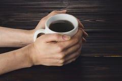 Vrouwenhanden die kop van koffie op houten lijst houden Royalty-vrije Stock Foto's