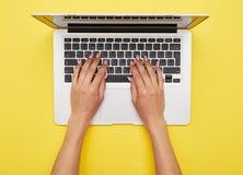 Vrouwenhanden die in laptop drukken die zich op gele achtergrond bevinden Royalty-vrije Stock Afbeeldingen