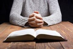 Vrouwenhanden die met een bijbel in dark over houten lijst bidden royalty-vrije stock fotografie
