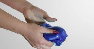 Vrouwenhanden die met vreemd genoeg het tevredenstellen van de blauwe substantie van slijmgooey spelen Antistress stock videobeelden