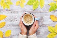 Vrouwenhanden die ochtendkop van koffie op de uitstekende houten lijst verfraaide hoogste mening van de herfst gele bladeren houd stock afbeeldingen