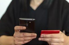 Vrouwenhanden die online betaling met smarthphone verrichten stock afbeeldingen