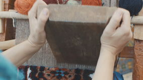 Vrouwenhanden die Oostelijk Tapijt weven openlucht stock video