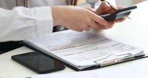 Vrouwenhanden die op calculator en het vullen documenten in modern bureau tellen stock video