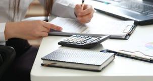 Vrouwenhanden die op calculator en het vullen documenten in modern bureau tellen stock footage