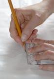 Vrouwenhanden die op het document het detail voor het naaien trasing Stock Afbeelding