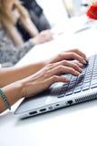 Vrouwenhanden die op laptop typen stock foto's
