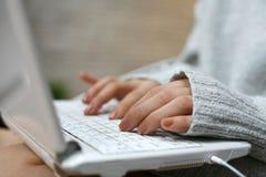 Vrouwenhanden die op laptop typen Stock Afbeeldingen