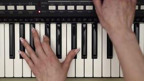 Vrouwenhanden die op synthesizer, hoogste mening dicht omhoog spelen stock footage