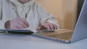 Vrouwenhanden die op toetsenbordnotitieboekje bij lijst typen Sluit omhoog vrouwelijke handen gebruikend laptop voor het verre we stock footage