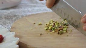 Vrouwenhanden die pistaches op houten scherpe raad snijden stock video