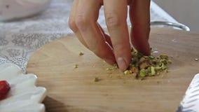 Vrouwenhanden die pistaches op houten scherpe raad snijden stock videobeelden