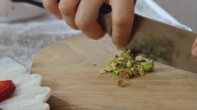 Vrouwenhanden die pistaches op houten scherpe raad snijden stock footage