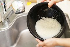 Vrouwenhanden die Rijst wassen stock foto's
