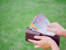 Vrouwenhanden die ringgit van geldmaleisië van portefeuille nemen royalty-vrije stock afbeeldingen