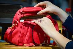 Vrouwenhanden die rode handtas openen stock afbeeldingen