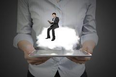 Vrouwenhanden die tablet met zakenmanzitting houden op wolk Stock Afbeelding