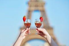 Vrouwenhanden die twee glazen wijn met de toren van Eiffel op de achtergrond houden Stock Fotografie