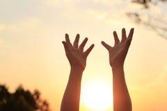 Vrouwenhanden die voor zegen op zonsondergangachtergrond bidden stock afbeelding