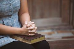 Vrouwenhanden in gebed op een Heilige Bijbel voor geloofsconcept dat worden gevouwen stock foto