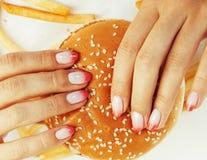 Vrouwenhanden met de hamburger van de manicureholding en frieten op wit, ongezond die voedsel worden geïsoleerd Royalty-vrije Stock Afbeeldingen
