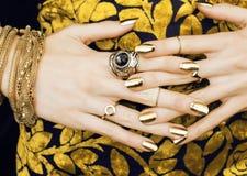 Vrouwenhanden met gouden manicurepartij van juwelen  royalty-vrije stock foto