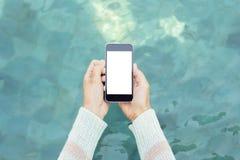 Vrouwenhanden met lege celtelefoon op een waterspiegelachtergrond, stock afbeelding