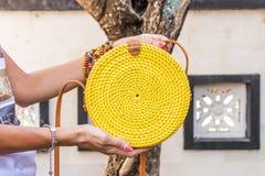Vrouwenhanden met modieuze modieuze gele rotanzak Tropisch Eiland Bali, Indonesië Rotanhandtas Royalty-vrije Stock Afbeelding