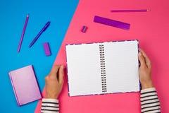 Vrouwenhanden met open notitieboekje en bureaulevering op kleurrijke achtergrond stock fotografie