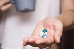 Vrouwenhanden met pillen en Mok water Royalty-vrije Stock Foto