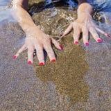 Vrouwenhanden op waterwaterkant, zwart zand Royalty-vrije Stock Foto