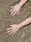 Vrouwenhanden op waterwaterkant, zwart zand Royalty-vrije Stock Foto's