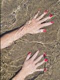 Vrouwenhanden op waterwaterkant, zwart zand Stock Fotografie