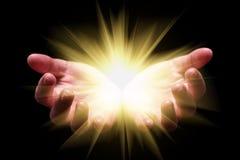 Vrouwenhanden tot een kom gevormde holding die, die of helder, gloeiend, stralend, het glanzen licht tonen afkomstig zijn stock afbeelding