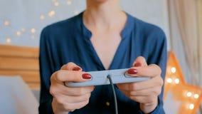 Vrouwenholding gamepad en het spelen videospelletjes thuis stock footage