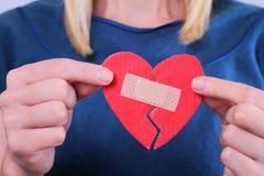 Vrouwenholding gebroken hart dicht omhoog vast door pleister Gevoel en emoties Liefdeproblemen, tweede kans, hoop, gevoel en emot Stock Foto's